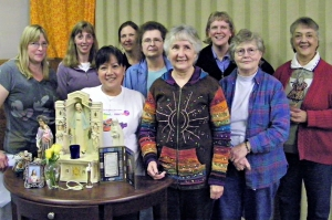 A few members of the St. Gregory's Women's Ministry are shown standing behind an example of a home altar. (Angie DelMoral)