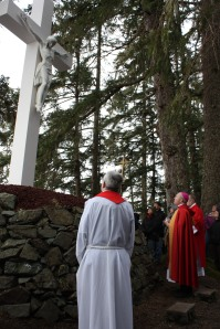 Bishop Burns blesses the outdoor cross at the Shrine of St. Therese following the annual Good Friday Stations of the Cross service.