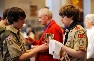 Boy Scouts serve as extraordinary ministers of holy Communion during a Catholic Scouting recognition Mass in 2010 at Sacred Heart Cathedral in Rochester, N.Y. The Boy Scouts of America voted May 23 to lift a ban on accepting openly gay Scouts as members, capping weeks of intense lobbying on both sides of the issue, the group said in a statement. (CNS photo/Mike Crupi, Catholic Courier)
