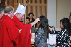 Bishop Edward Burns confirms a young woman at St. Paul the Apostle Church in Juneau, May of 2011.