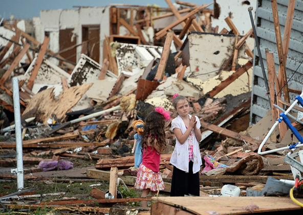 Two girls stand in rubble after a tornado struck Moore, Okla., May 20. The mile-wide tornado touched down near Oklahoma City, killing dozens, including many children, destroying homes, businesses and a pair of elementary schools in the suburb of Moore. (CNS photo/Gene Blevins, Reuters)