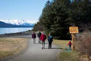 Visitors walk along causeway after visiting chapel on Shrine Island at Shrine of St. Therese in Juneau, Alaska