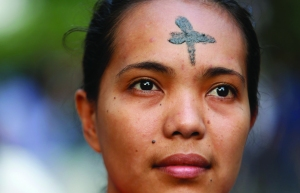 Woman with cross marked on forehead looks on during Ash Wednesday Mass outside church in Manila
