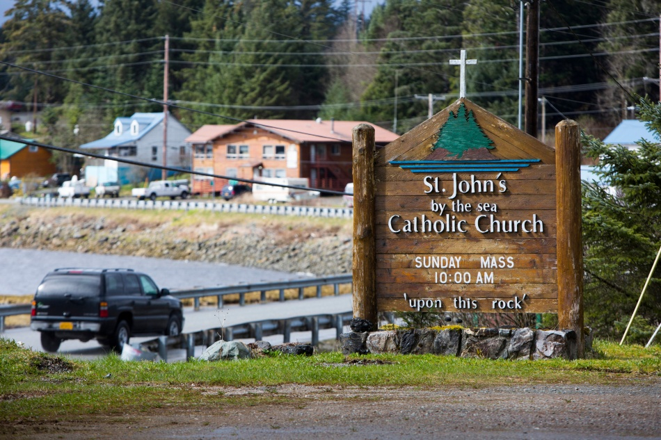 In this April 16, 2014 file photo, a vehicle drives past a St. John by the Sea Church sign off the main road leading to Klawock and Craig on Prince of Wales Island in southeastern Alaska. Catholics make up slightly less than 2 percent of the island's 6,000 residents. The island is accessible only by boat, ferry or sea plane. (CNS photo/Nancy Wiechec)