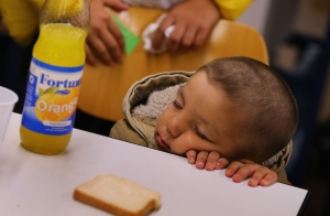 "A refugee child from Iraq falls asleep at a table inside a shelter in Wertheim, Germany, Sept. 14. ""Do not abandon victims"" of conflicts in Syria and Iraq, Pope Francs said. (CNS photo/Karl-Josef Hildenbrand, Reuters)"